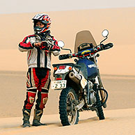 Lonely adventurous female motorcyclist riding motorbike alone in the African desert, Sudan, Africa