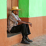 Portrait of old Cuban man sitting in front of pastel coloured house front in the streets of Trinidad, Cuba